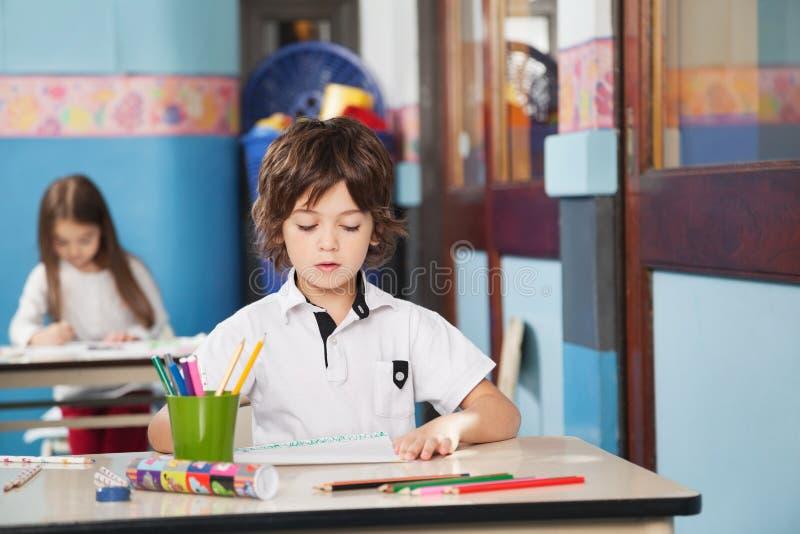有颜色铅笔和画纸的男孩在 免版税图库摄影