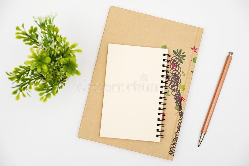 有颜色铅笔的顶面看法笔记本在白色桌上 免版税图库摄影