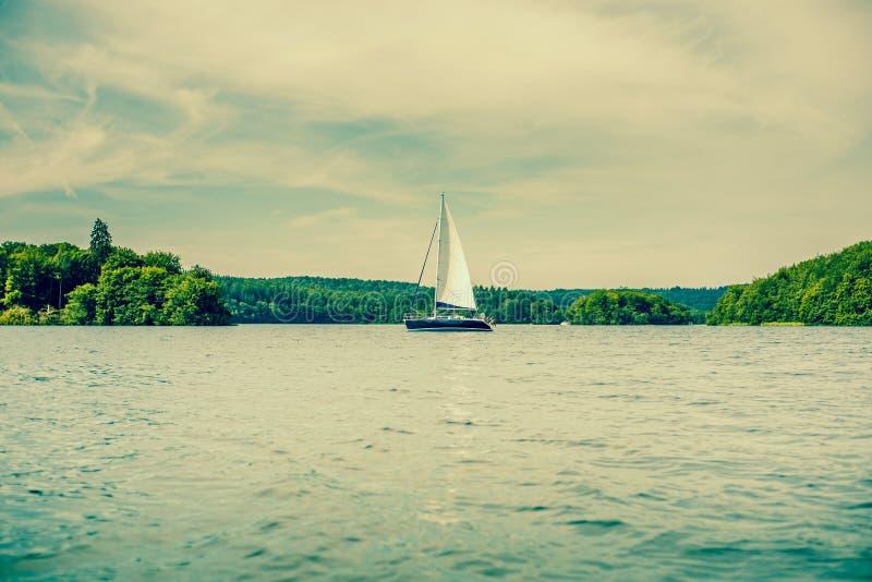 有风帆的小船在湖 免版税库存图片