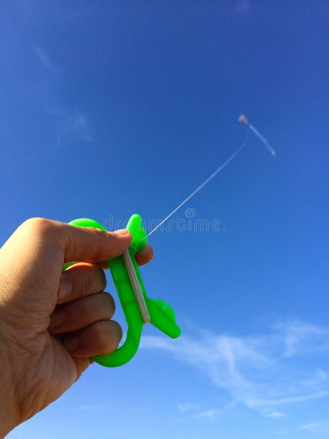 有风筝的手反对天空 免版税图库摄影