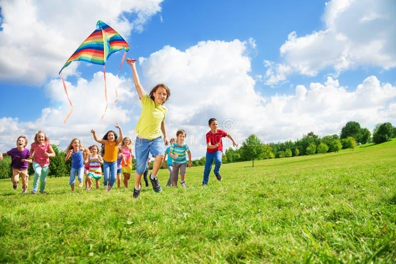 有风筝的男孩和朋友 免版税库存图片