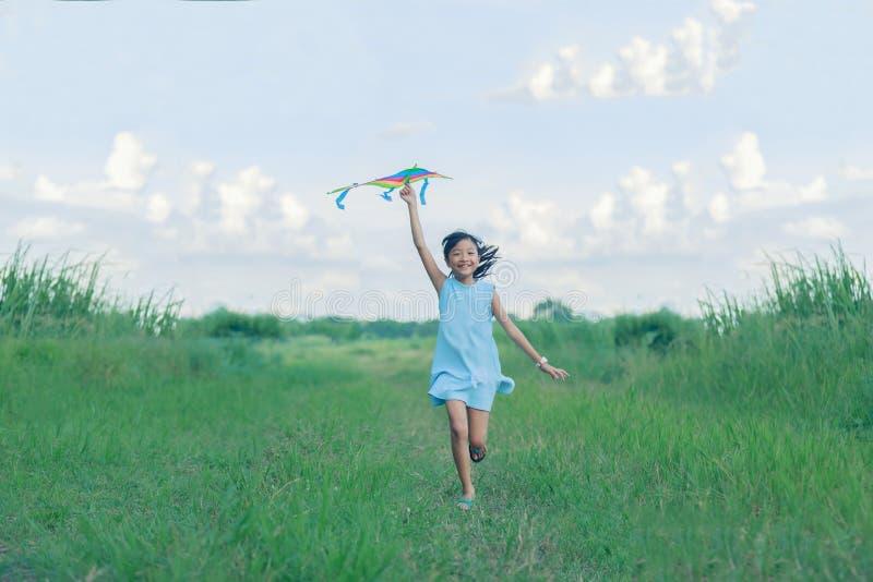 有风筝赛跑的亚洲儿童女孩和愉快在summ的草甸 免版税库存图片