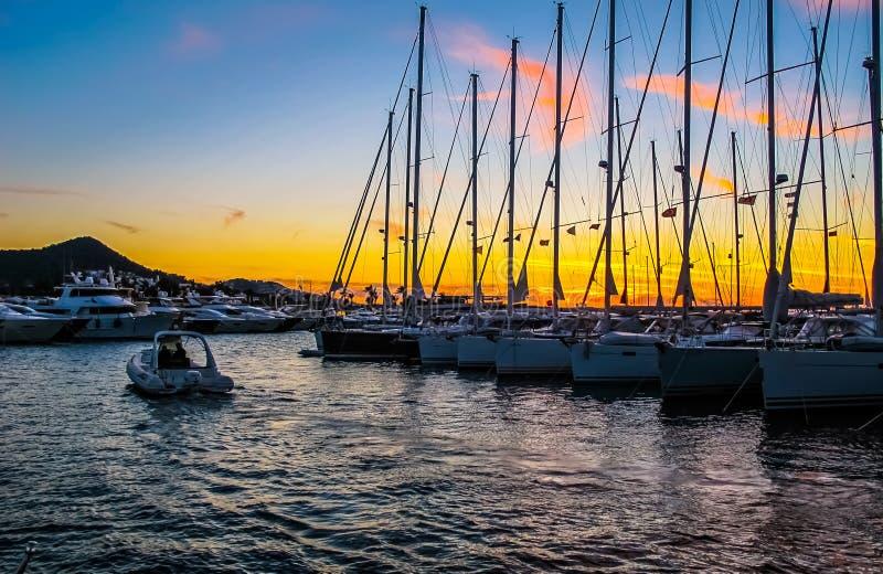 有风船和游艇的小游艇船坞在美好的日落 免版税库存照片
