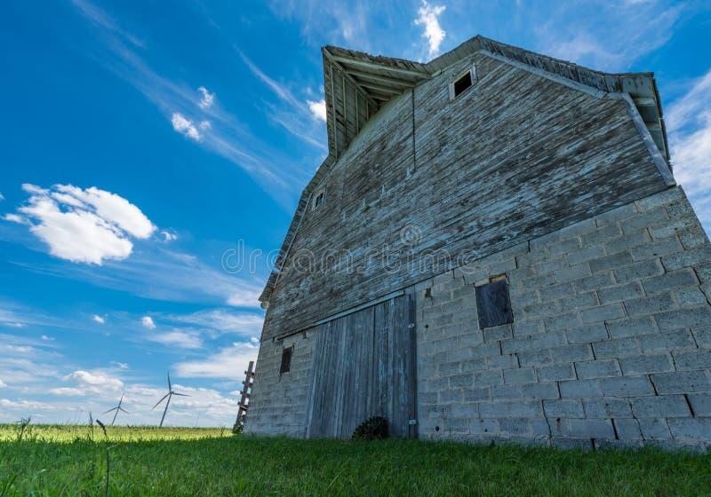 有风轮机的老被风化的谷仓在背景中 免版税图库摄影