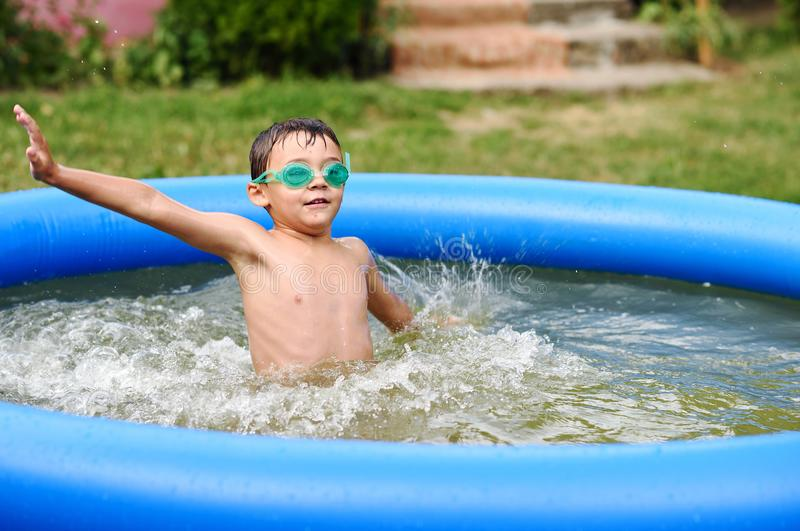 有风镜的年轻男孩在游泳池 库存图片