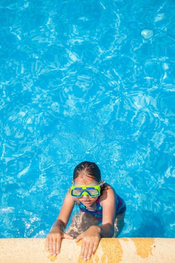 有风镜的愉快的女孩在游泳池 图库摄影