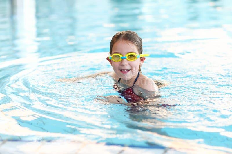 有风镜的女小学生在游泳池 免版税库存照片