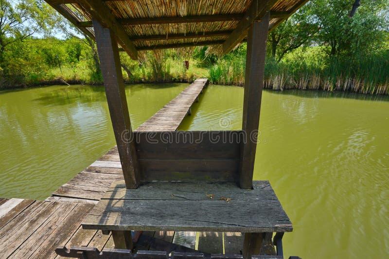 有风雨棚的渔地方在从Hanul Pescarilor餐馆的湖在奥拉迪亚 免版税库存照片