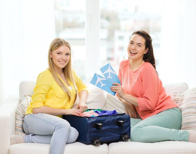有飞机票的两个微笑的十几岁的女孩 免版税库存图片