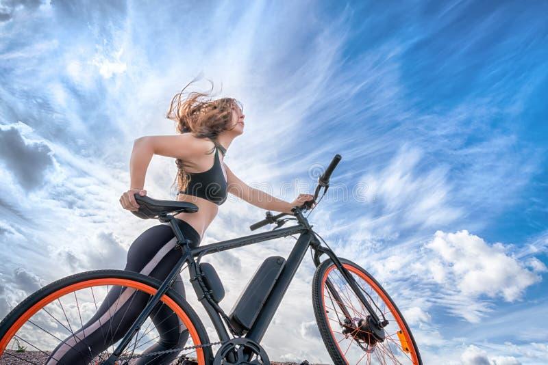 有飞行在风的头发的运动女孩带领电自行车 免版税库存照片
