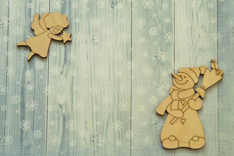 有飞行天使笤帚和红腹灰雀和葡萄酒形象的微笑的种类木雪人与星的在明亮的冬天背景 免版税图库摄影