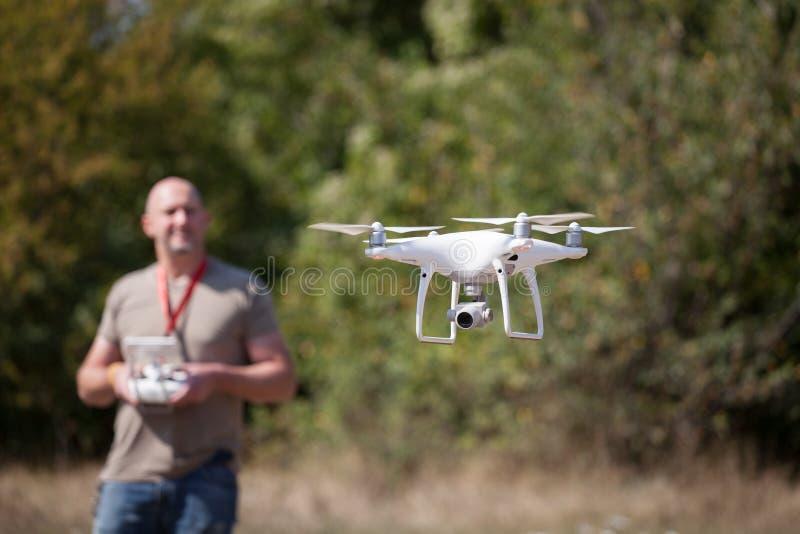 有飞行寄生虫的人在公园 有遥远的控制器的人在他的采取空中照片和录影的手上 免版税库存图片