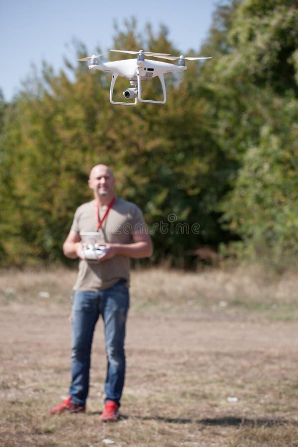 有飞行寄生虫的年轻人在公园 有遥远的控制器的人在他的采取空中照片和录影的手上 免版税库存图片