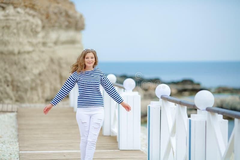有飞行红色头发的愉快的舞女在城市堤防,享受生活概念 走愉快地笑的年轻女人  免版税库存照片