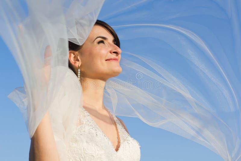 有飞行面纱的可爱的微笑的新娘 库存图片