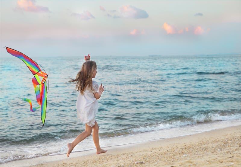 有飞行风筝的小女孩在日落的海滩 库存图片