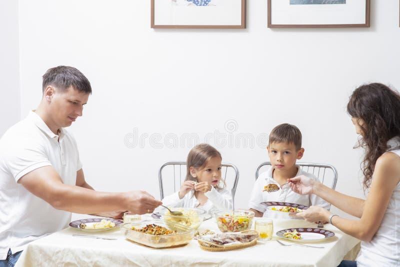 有食用他们的孩子的愉快的父母早餐在家 库存照片