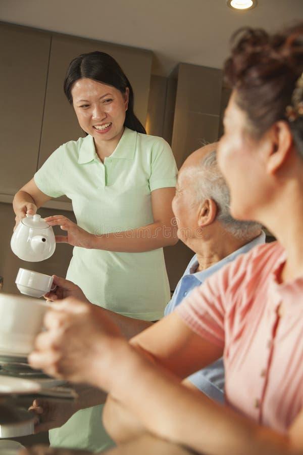 有食用成人的女儿的父母早餐 免版税库存照片
