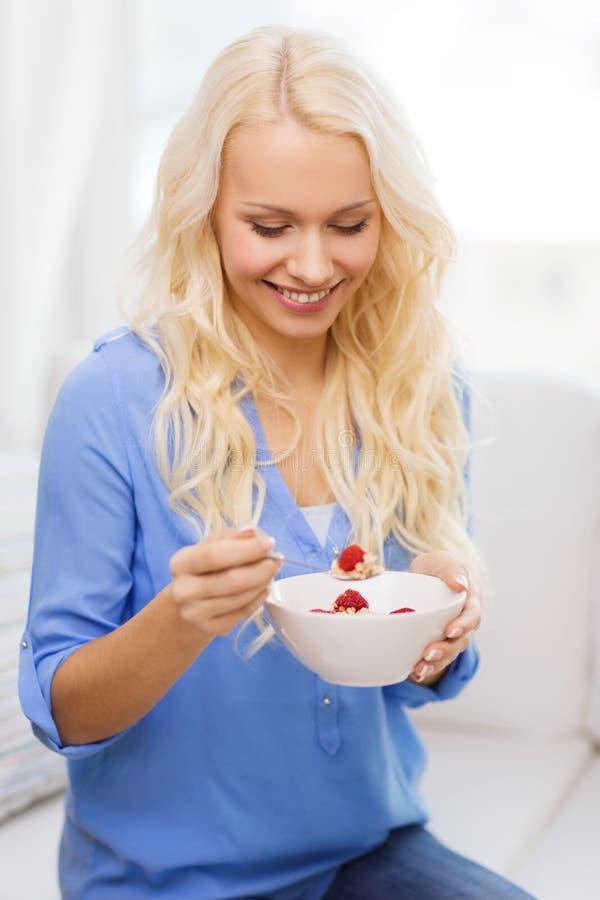 有食用碗的微笑的妇女的muesli早餐 免版税库存照片