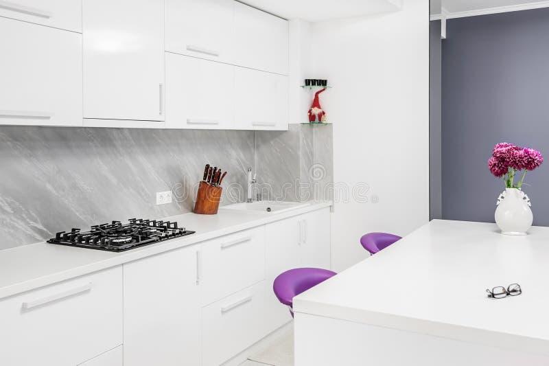 有餐桌和紫色椅子的现代厨房 库存照片