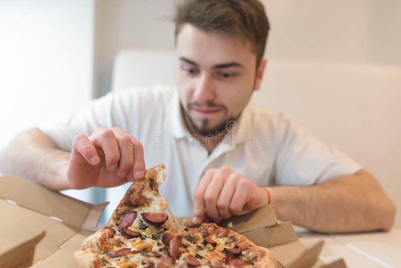 有饥饿的神色的一个英俊的人拉紧比萨饼在箱子外面并且将吃它 免版税图库摄影