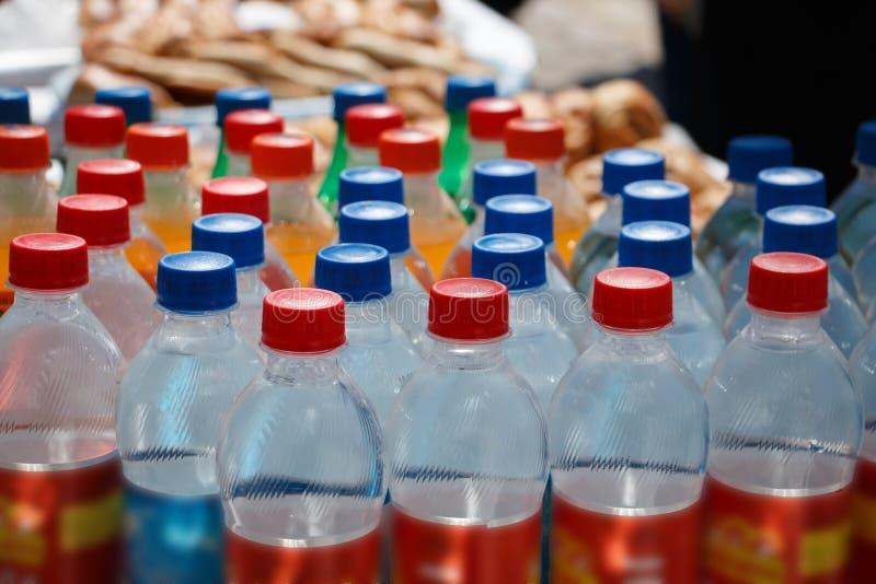 有饮料和五颜六色的盒盖的塑料瓶 免版税库存照片