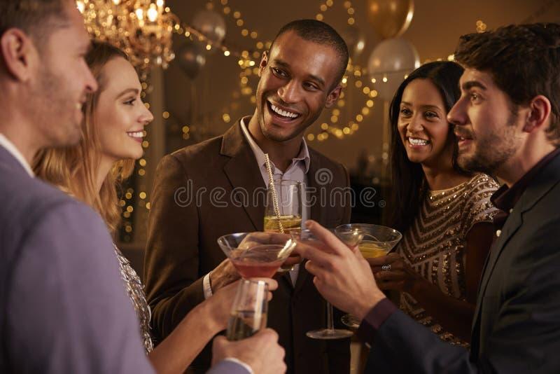 有饮料的朋友享受鸡尾酒会的小组  库存图片