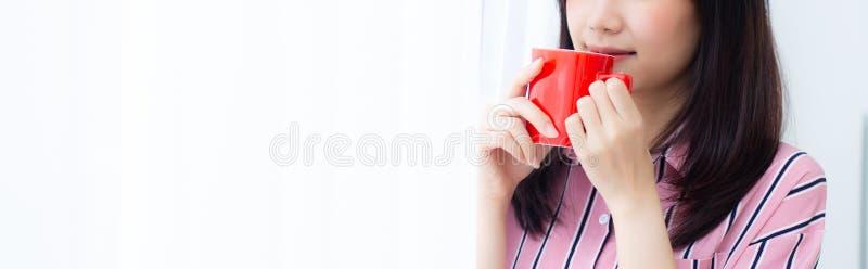 有饮料的特写镜头年轻亚裔妇女每咖啡身分帷幕窗口背景在卧室 图库摄影