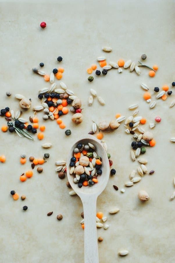 有香料、谷物和豆的混合的木匙子在土气背景 免版税库存照片