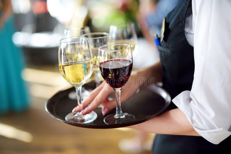 有香槟和酒杯盘的女服务员  免版税库存照片