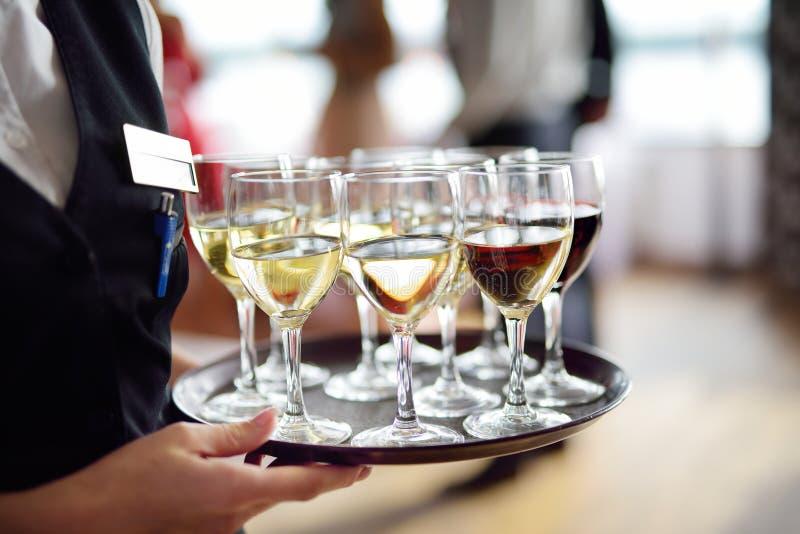 有香槟和酒杯盘的女服务员  免版税图库摄影