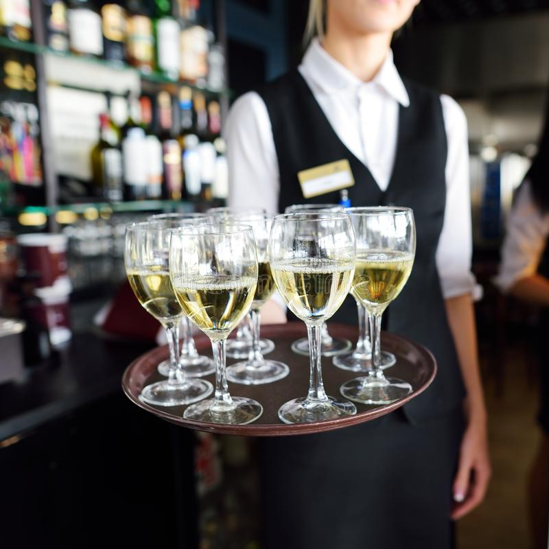有香槟和酒杯盘的女服务员  库存照片