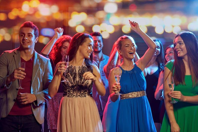 有香槟跳舞的愉快的朋友在夜总会 免版税库存图片