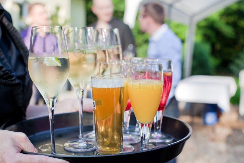 有香槟, cocлtails,啤酒盘的等候人员  免版税库存图片