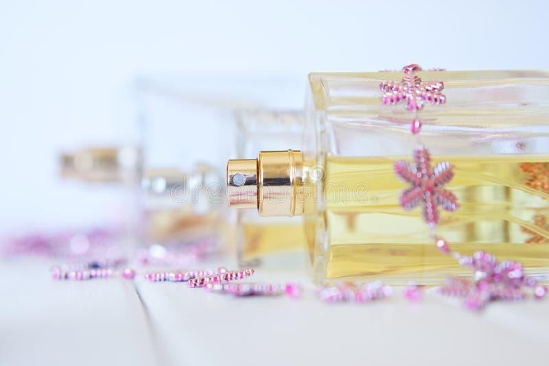 有香水喷子的透明瓶说谎白色表面上 秀丽产业 库存照片