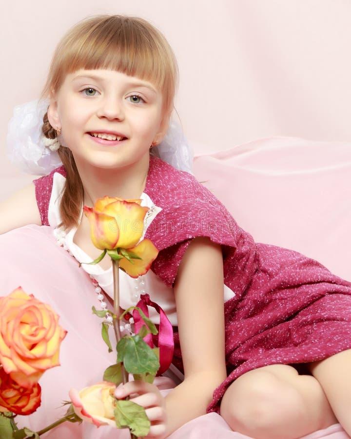 有香水月季花束的女孩  免版税库存图片