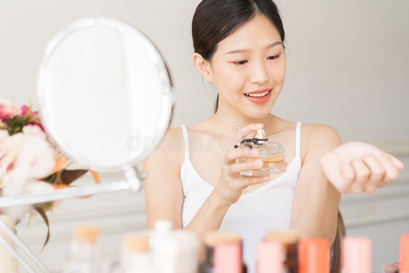 有香水的亚裔女孩,应用在她腕子和嗅到的年轻女人香水 免版税库存图片