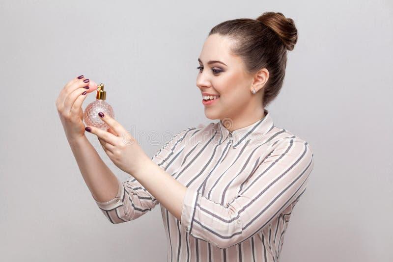有香水的女孩 镶边衬衣藏品瓶的特写镜头侧视图画象美丽的年轻女人相当微笑的女孩香水 图库摄影