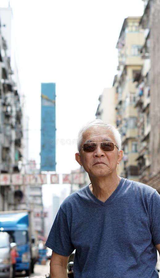 有香港都市建筑学场面的老人 免版税库存照片