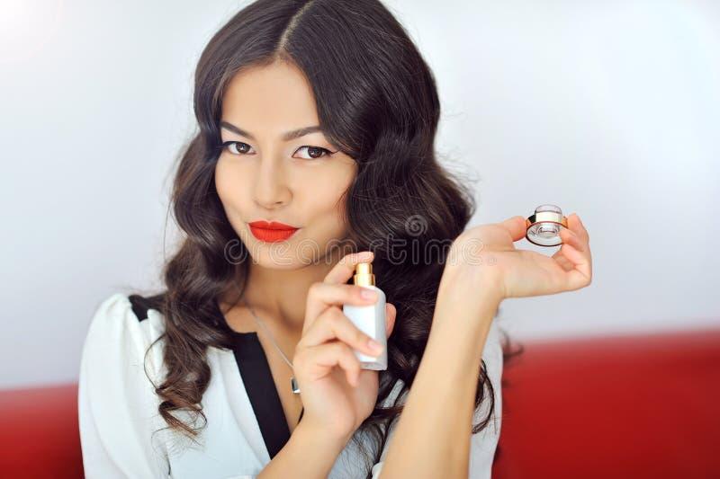 有香水的妇女,举行瓶perfu的年轻美丽的女孩 图库摄影