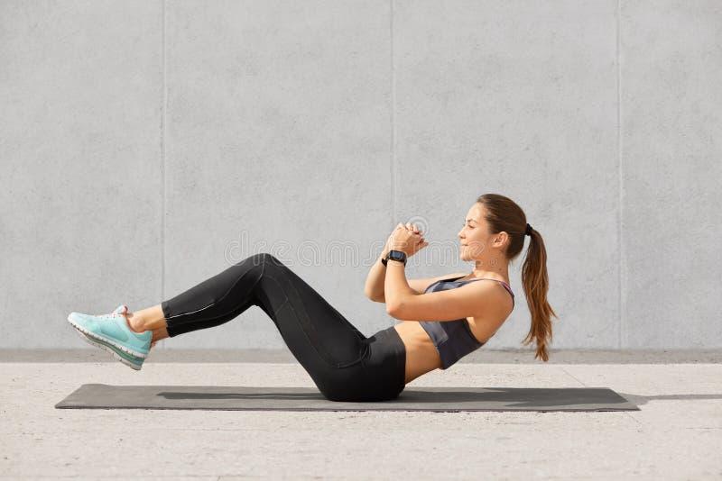 有马尾的依据自决的运动的妇女,穿戴在绑腿,上面,运动鞋, smartwatch在新闻做,要有肌肉 图库摄影