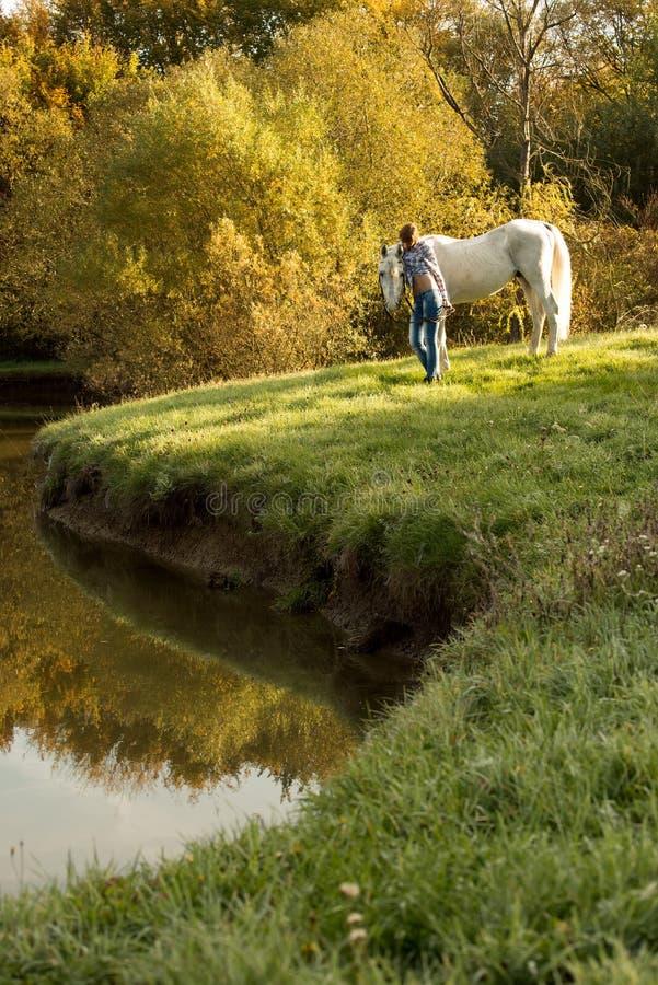 有马的少妇在湖 免版税库存照片
