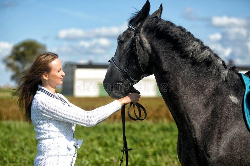 有马的白肤金发的妇女 免版税图库摄影