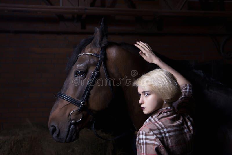 有马的美丽的少妇 免版税库存图片