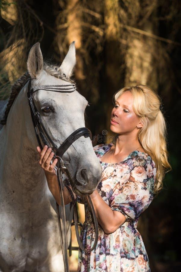 有马的美丽的白肤金发的妇女 免版税库存图片