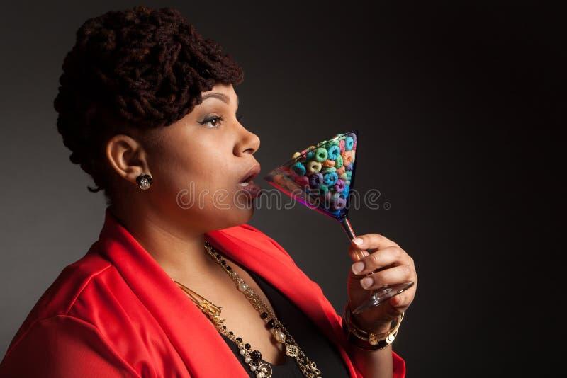 有马蒂尼鸡尾酒杯的非裔美国人的妇女水果的谷物 图库摄影