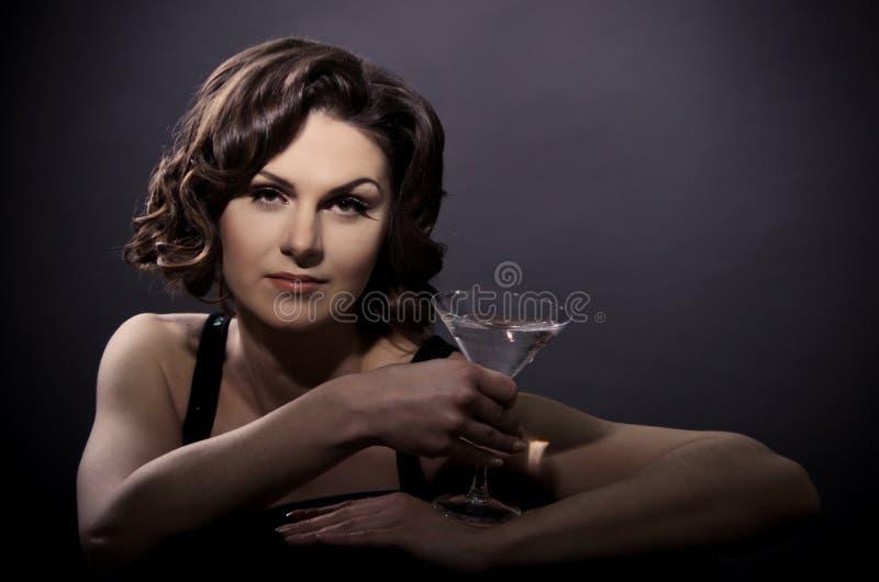 有马蒂尼鸡尾酒玻璃的美丽的性感的妇女 免版税库存照片