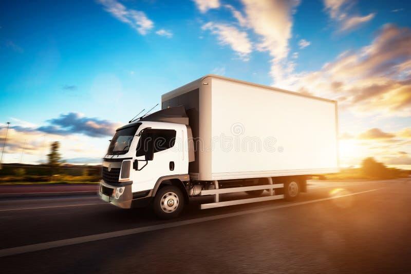 有驾驶在高速公路的空白的白色拖车的商业货物送货卡车 免版税库存照片