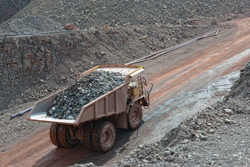 有驾驶在quary的被装载的石头的倾销者卡车 开采 免版税库存图片