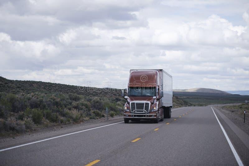 有驾驶长的内华达高速公路的拖车的布朗现代半卡车 库存照片